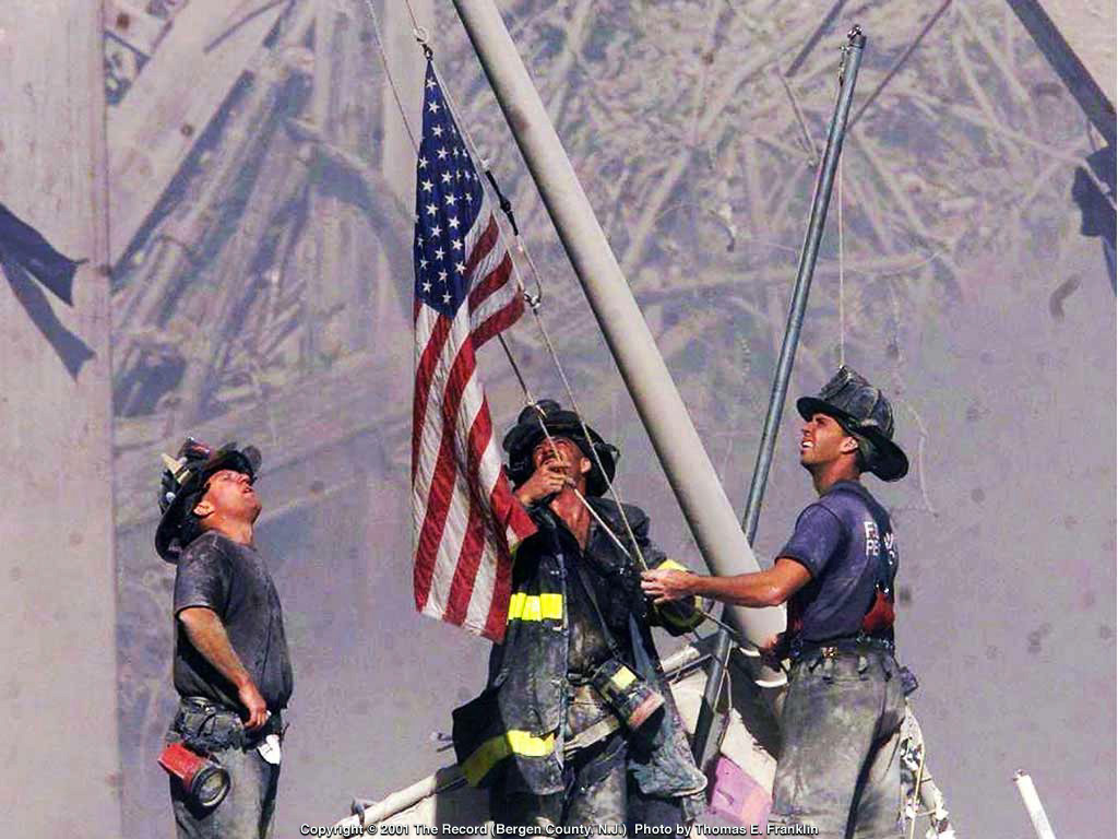 Fire fighters raise flag on 9-11. Americans were strong on 9-11-01